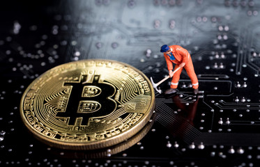Bitcoin mining miniature worker, small figure holding mattock digging on shiny golden Bitcoin crypto currency coin on electronics cyber look circuit board with soldering Fototapete