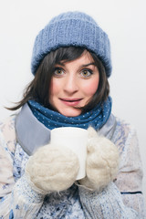 Portrait of cute woman in winter clothes holding cup with tea on white background