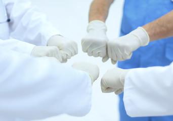 Doctors and nurses coordinate hands.
