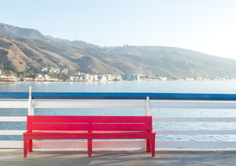 solitary red wooden bench against blue and white railing overlooking the Pacific ocean in Malibu, California