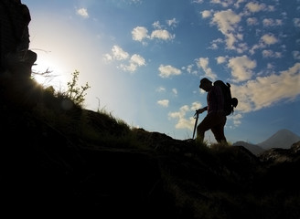 Silhouette of a man hiking in mountains with backpack.