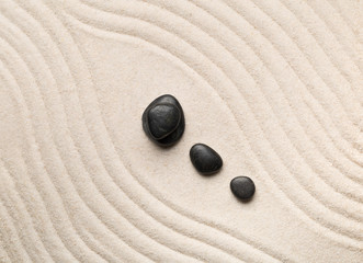 Poster Stones in Sand Zen sand and stone garden with raked curved lines. Simplicity, concentration or calmness abstract concept