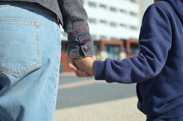 The child holds mum. Closeup on hands over sunny day outdoors background. Caring happiness