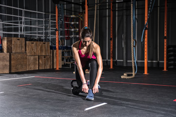 Athletic girl ready to start exercises with a kettlebell at the gym