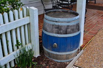 Porch scene with and old wooden barrel and a white picket fence.