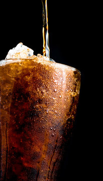 Soft drink pouring to glass with crushed ice cubes isolated on dark background with copy space. There is a drop of water on the transparent glass surface.