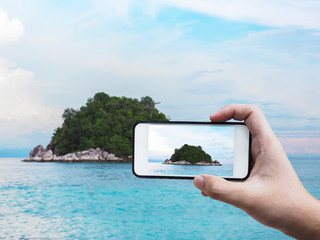 hand holding mobile phone taking picture of island
