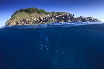 Scuba diving underwater beside tropical island