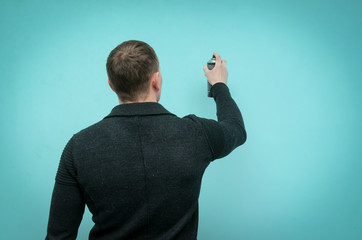 Rear view of a man drawing a graffiti on a wall with a ballon with paint isolated on blue background.