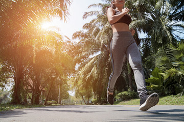 Young fitness sports woman runner running on tropical park trail