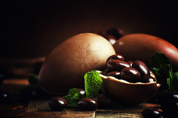 Easter composition with brown chocolate eggs, vintage wooden background, selective focus