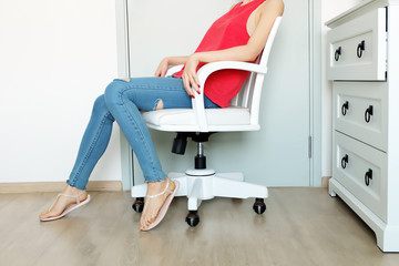 Close Up Sit on White Chair Studio. Beautiful Woman Wearing Red Shirt, Lack of Jeans and Shoes Sitting on a White Chair in the Room White Studio Background Great for Any Use.