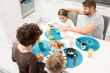 High angle portrait of happy young family with two children enjoying breakfast at home sitting at dinner table in cozy kitchen in morning