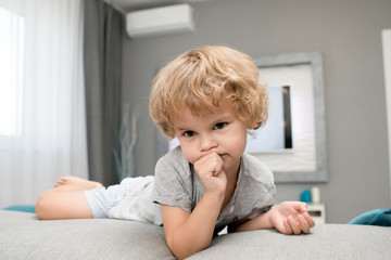 Portrait of adorable curly little boy sucking thumb climbing on sofa in modern living room apartment