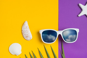 Wall Mural - Set of summer object sunglasses sky reflect, star fish,shell and palm leaf on vivid yellow purple background.Holiday vacation backdrop.Copy space for display of product or content design.