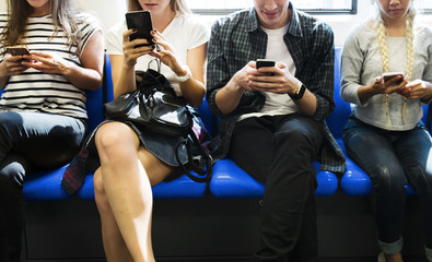 Group of young adult friends using smartphones in the subway