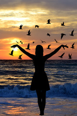 Young woman silhouette with birds on the seaside