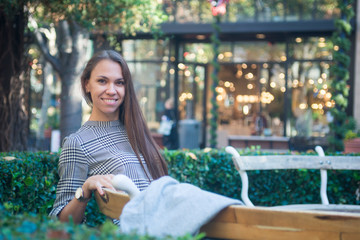 Smiling happy woman sitting on the bench in the city