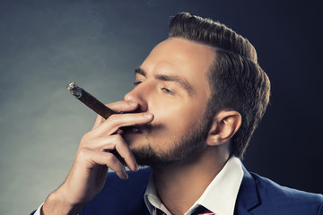 Man with cigar in hand. Modern hair style, handsome face of male model over dark background