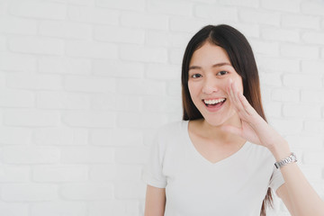 Happy smiling beautiful Asian woman gesturing with hand to telling in a white brick wall background.