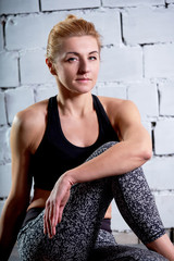Close-up portrait sportsgirl photos. Young woman blonde sits look into the camera after training.