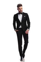 young fashion man in tuxedo walks and looks down