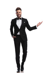 happy young elegant man presenting or welcoming