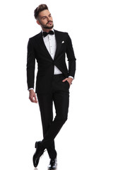 man in tuxedo standing with hand in pocket looks away