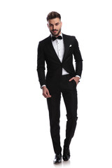 smiling man in tuxedo stands with one hand in pocket