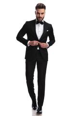 serious fashion model buttoning his tuxedo while walking