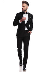 man in tuxedo wearing ring, walks and looks to side