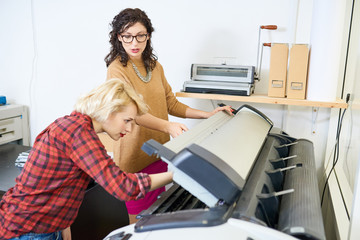 Portrait of two women setting up plotter machine in printing shop, focus on  manager giving instructions to employee, copy space