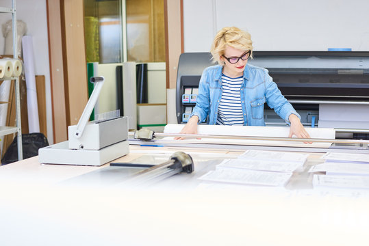 Portrait of blonde young woman working in modern printing shop or publishing company, cutting  paper and loading plotter machines, copy space