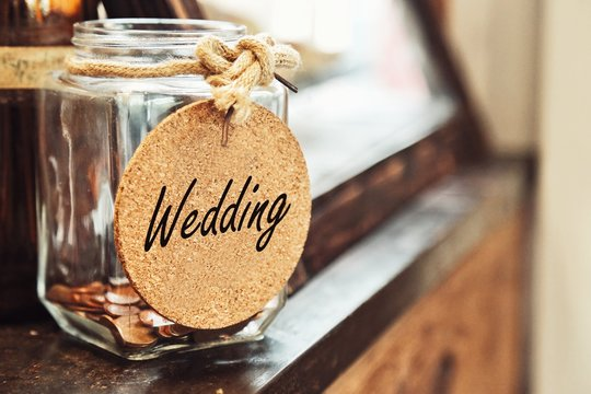 Vintage retro glass jar with hemp rope tie wedding tag and few coins inside on wood counter concept of saving money for wedding