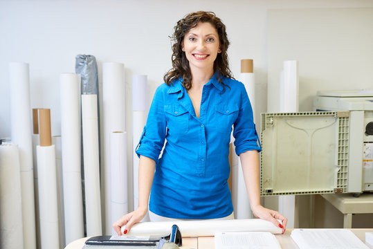 Portrait of smiling operational manager looking at camera posing in printing shop or publishing company standing  against paper rolls