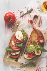 Caprese sandwich with mozzarella, tomato and basil on a wooden board. Italian cuisine concept.