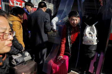 People enter and leave a ticket office at the Beijing Railway Station during the annual Spring Festival travel rush ahead of the Chinese Lunar New Year in Beijing