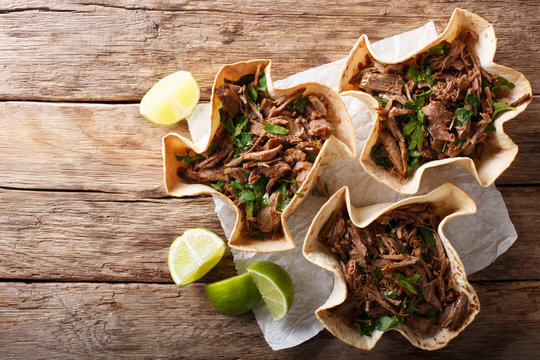 Pulled beef with lime and greens in a corn tortillas close-up on a table. horizontal top view