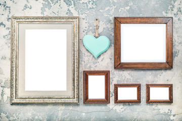 Photo or picture frames blanks and handmade wooden love heart hanging on vintage aged grunge textured concrete wall background. Retro old style filtered photo