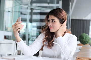 Selective focus on mobile smart phone in hands of attractive young Asian woman taking photo or selfie in office.