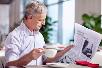 Old fashioned manner. Attractive pleased mature man sitting at the table while holding coffee and reading newspaper