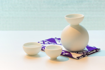 Set for Japanese sake on a napkin with a Japanese pattern on a white table.