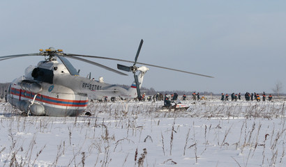 Russian Emergency Situations Ministry members work at the crash site of the AN-148 airplane in Moscow Region