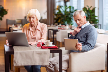 Gadget for everyone. Thoughtful nice mature couple sitting on chairs and looking at screens while using tablet and laptop