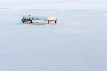 single bench covered with snow, winter day