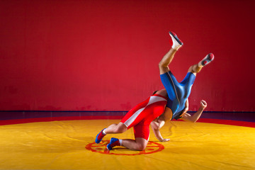 Two young men in blue and red wrestling tights are wrestlng and making a hip throw on a yellow wrestling carpet in the gym