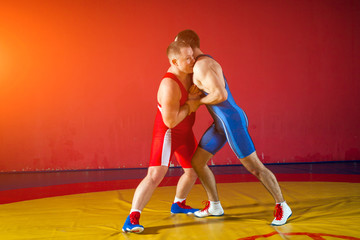 Two strong wrestlers in blue and red wrestling tights are wrestlng on a yellow wrestling carpet in the gym. Young man doing grapple.