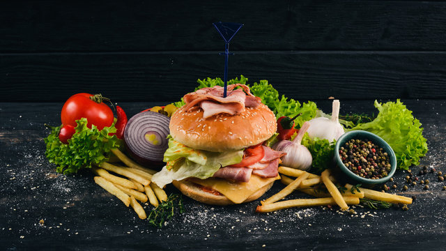 Burger with bacon, cheese and lettuce. American Traditional Food. On a black wooden background. Copy space.