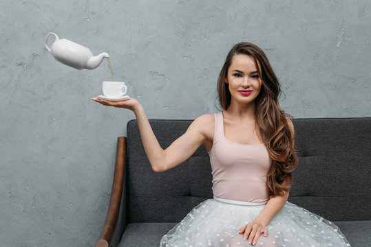 beautiful woman smiling at camera and holding cup while levitating teapot pouring tea