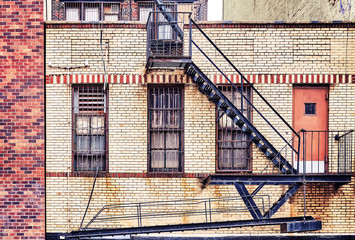 Vintage toned picture of an old brick building with fire escapes, Manhattan, New York City, USA.